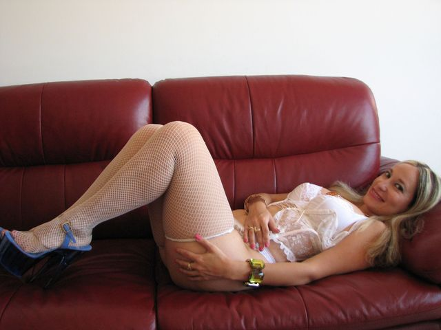 Hot, busty MILF Emanuelle in white lingerie and fishnet stockings